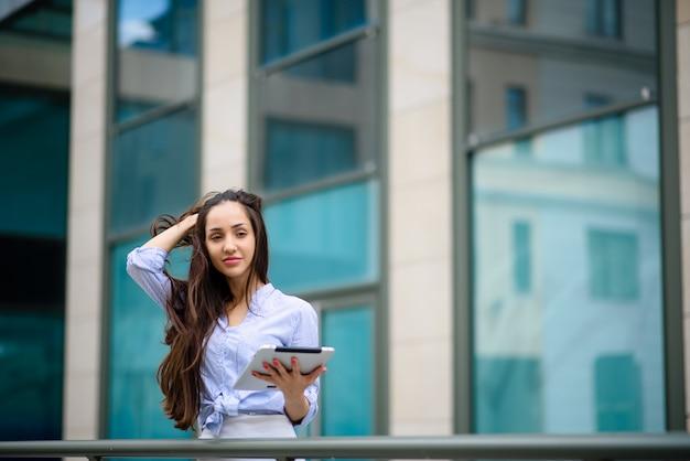 Linda garota sorrindo e funcionando em um tablet.