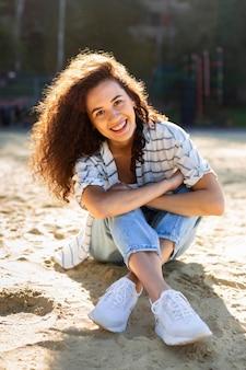 Linda garota sorrindo enquanto está sentada na areia