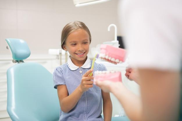 Linda garota sorrindo. menina alegre e bonita sorrindo enquanto segura a escova de dentes e vai ao dentista
