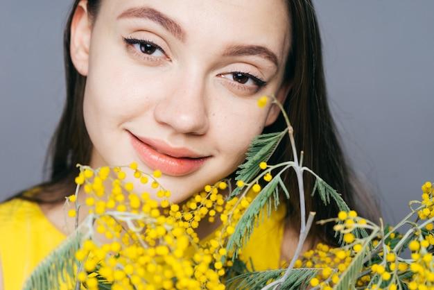Linda garota sorrindo, segurando um grande buquê de mimosa amarela