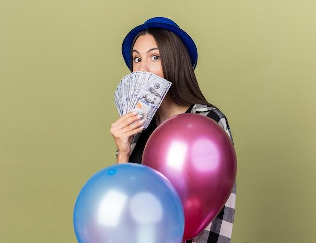 Linda garota surpresa com chapéu azul em pé atrás de balões, rosto coberto com dinheiro isolado na parede verde oliva