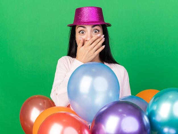 Linda garota surpresa com chapéu de festa em pé atrás de balões cobrindo a boca com a mão