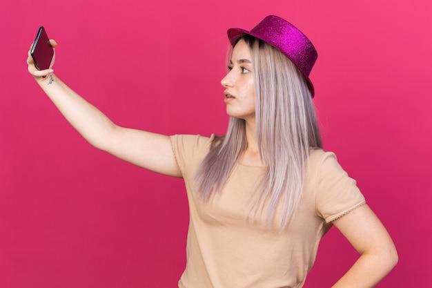 Linda garota surpresa com chapéu de festa tirando uma selfie isolada na parede rosa