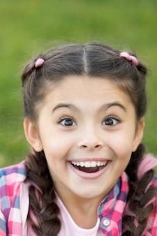 Linda garota surpresa com um sorriso no rosto expressão de felicidade momento de inesperado olhando