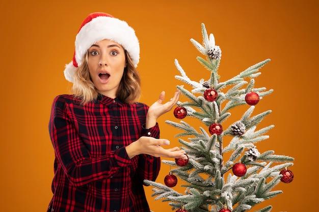 Linda garota surpresa em pé perto de uma árvore de natal, usando um chapéu de natal isolado em um fundo laranja