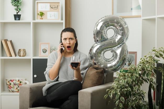 Linda garota surpresa no dia da mulher feliz segurando uma taça de vinho e fala sobre o vinho, sentada na poltrona na sala de estar