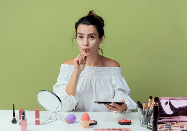Linda garota surpresa se senta à mesa com ferramentas de maquiagem segurando uma paleta de sombras e um pincel de maquiagem isolado na parede verde