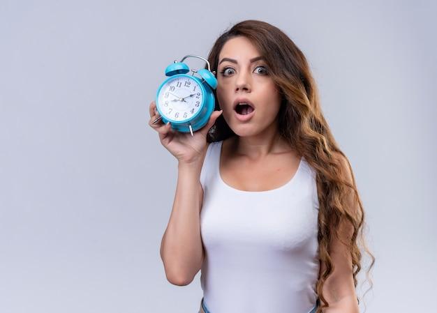Linda garota surpresa segurando o despertador na parede branca isolada com espaço de cópia