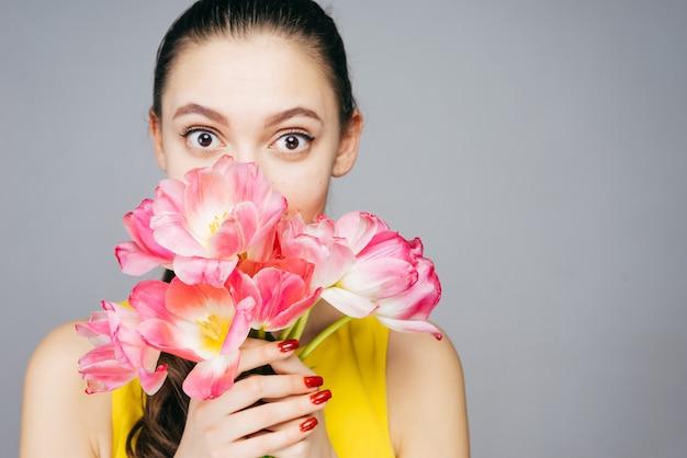 Linda garota surpresa, segurando um buquê de flores rosa perfumadas