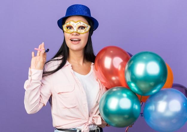 Linda garota surpresa usando chapéu de festa e máscara de baile de máscaras segurando balões com apito de festa