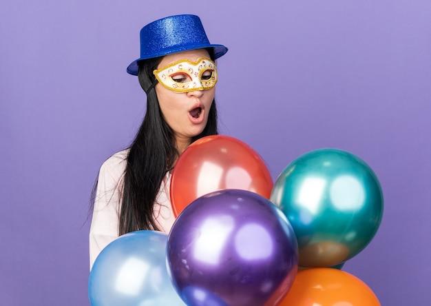 Linda garota surpresa usando chapéu de festa e máscara de baile de máscaras segurando e olhando para balões isolados na parede azul
