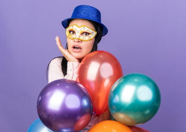 Linda garota surpresa usando chapéu de festa e máscara de máscara em pé atrás de balões, colocando a mão sob o queixo, isolado na parede azul