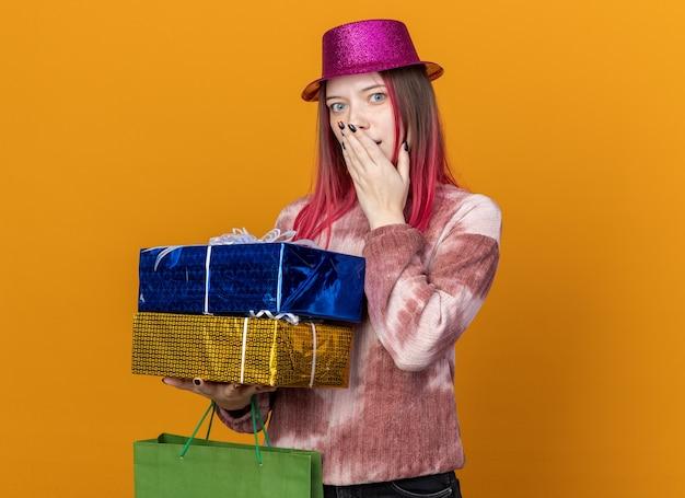 Linda garota surpresa usando um chapéu de festa segurando uma sacola de presentes com caixas de presente cobrindo o rosto com a mão