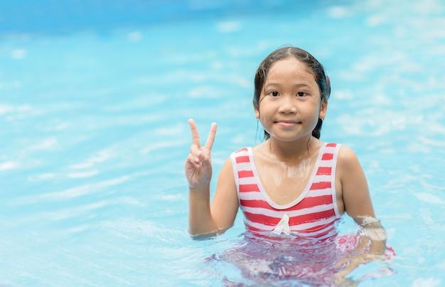 Linda garota tem se sentindo engraçado na piscina.