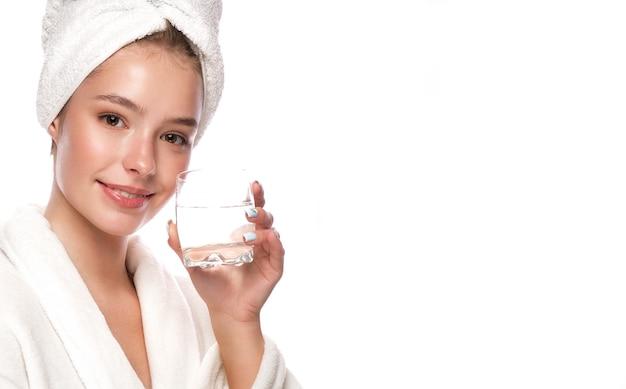 Linda garota tenra em uma toalha branca com pele limpa, fresca, posando na frente da câmera. rosto bonito. cuidados com a pele. foto tirada em estúdio em um fundo branco e isolado.