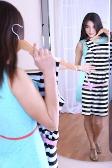 Linda garota tentando se vestir perto de um espelho no quarto