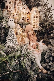 Linda garota tira fotos em uma decoração de natal com muitas árvores sob a neve e luzes