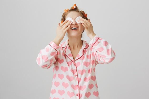 Linda garota tirando a maquiagem antes de dormir com almofada de algodão, usando rolinhos de cabelo e pijama