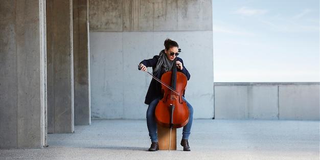 Linda garota toca violoncelo com paixão em um ambiente concreto