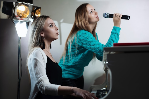 Linda garota tocando piano e sua amiga canta no microfone