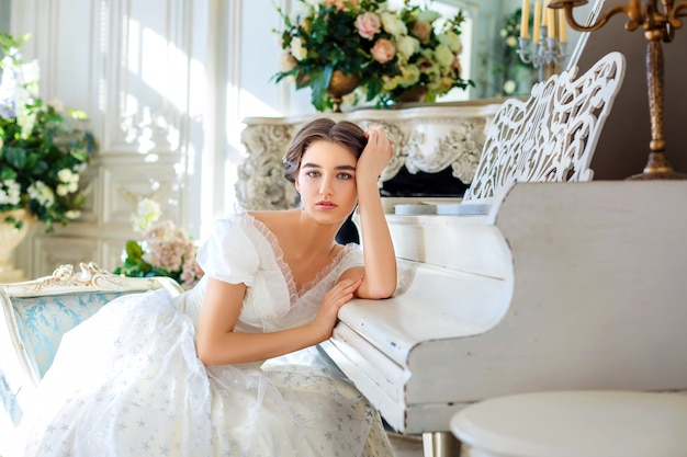Linda garota tocando piano, em um lindo vestido no interior
