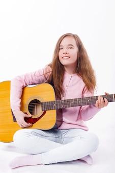 Linda garota tocando violão e olhando para a câmera sobre o branco