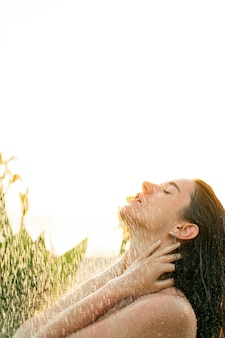 Linda garota toma uma ducha tropical ao ar livre ao pôr do sol. cuidados de higiene e beleza. tratamentos de água de spa.