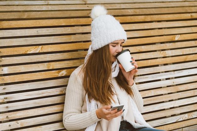 Linda garota tomando café, chá de caneca plástica no inverno e falando no celular