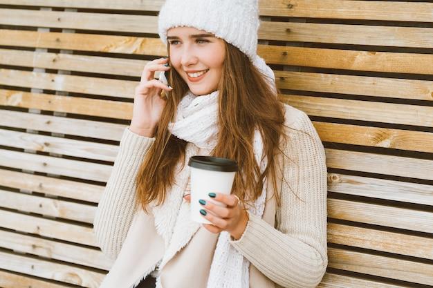Linda garota tomando café, chá de caneca plástica no outono, inverno e falando no celular.