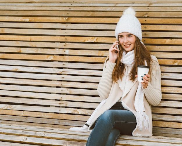 Linda garota tomando café, chá de uma caneca de plástico no outono, inverno e conversando