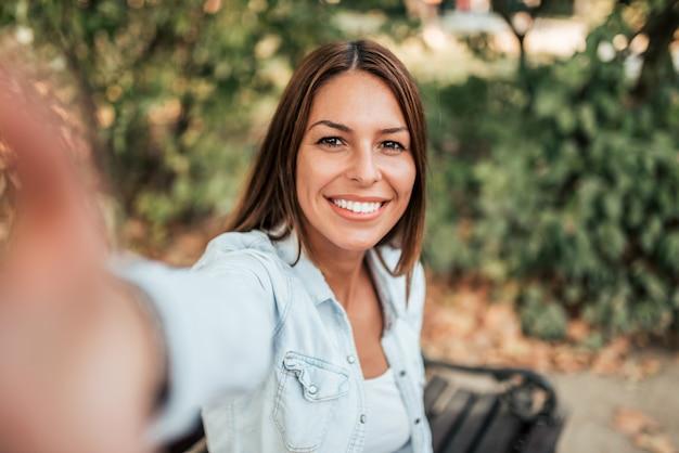 Linda garota tomando selfie no parque.