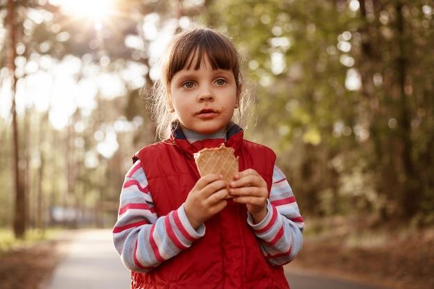 Linda garota tomando sorvete caminhando na floresta
