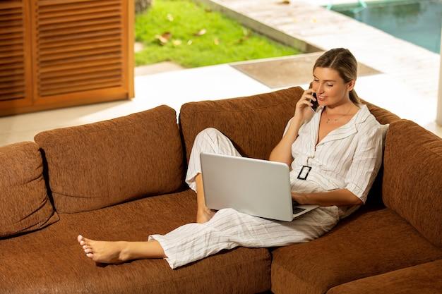 Linda garota trabalha em casa no computador.