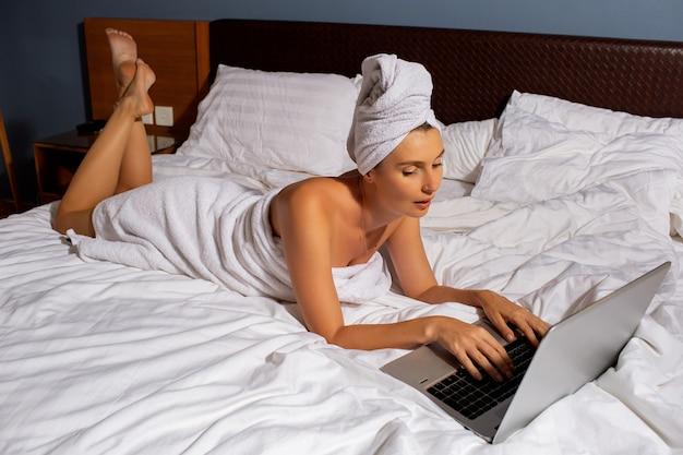Linda garota trabalha em um computador na cama.
