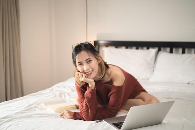 Linda garota trabalhando com o laptop na cama, conceito de trabalho em casa