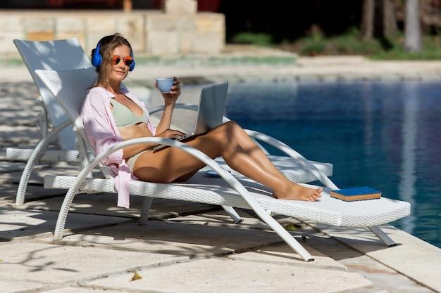 Linda garota trabalhando no computador perto da piscina