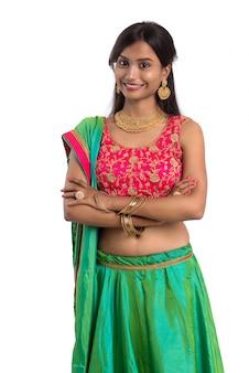 Linda garota tradicional indiana posando na superfície branca.