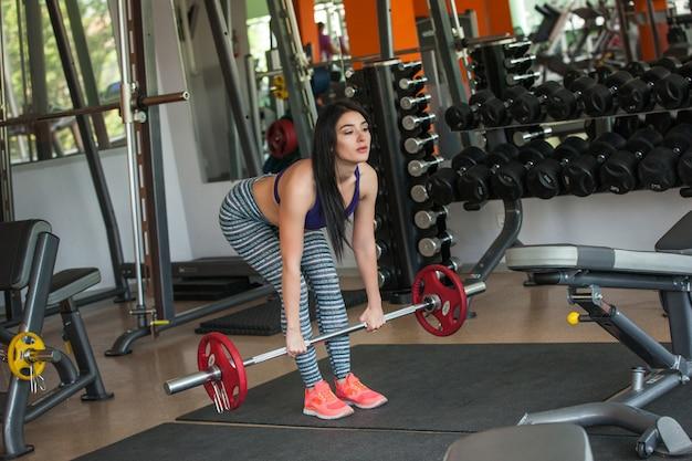 Linda garota treinando na academia com barra. jovem mulher bonita fazendo exercício