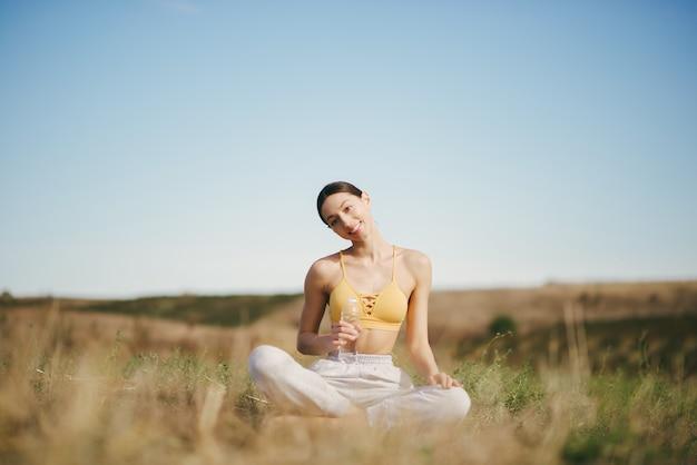 Linda garota treinando no céu azul em um campo