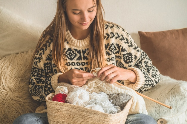 Linda garota tricota um suéter quente em cima da cama. tricotar como hobby. acessórios para tricô.