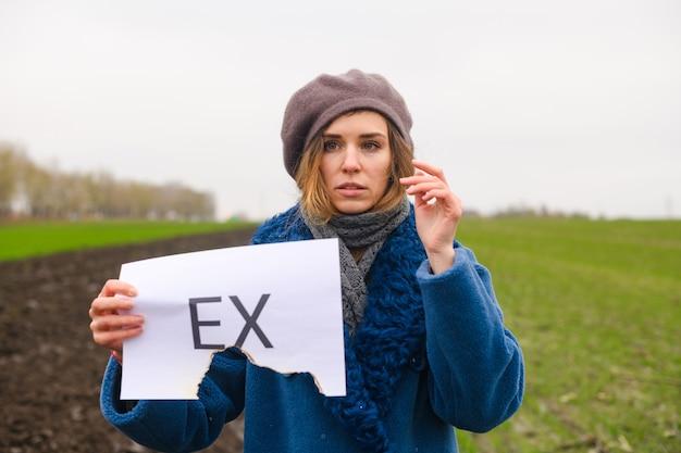 Linda garota triste segurando um papel branco meio queimado com um texto impresso ex sobre separação, divórcio com namorado, marido