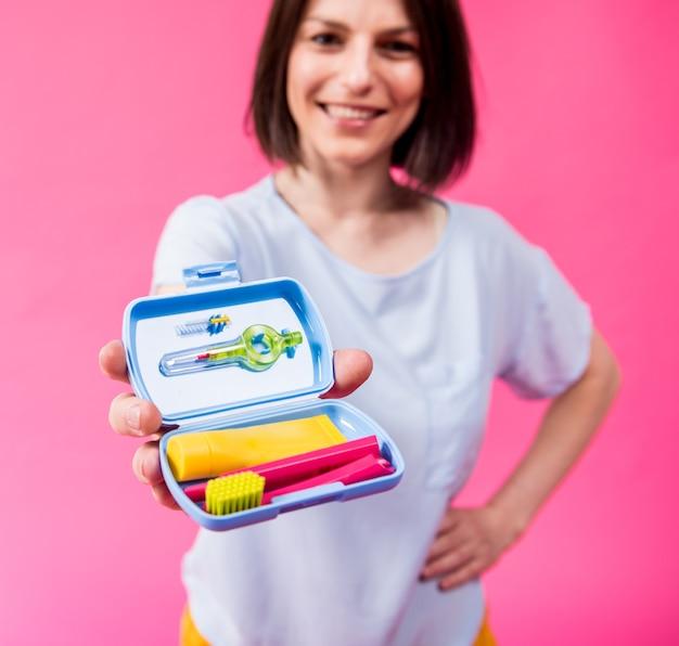 Linda garota usa um kit de viagem para atendimento odontológico em um fundo rosa