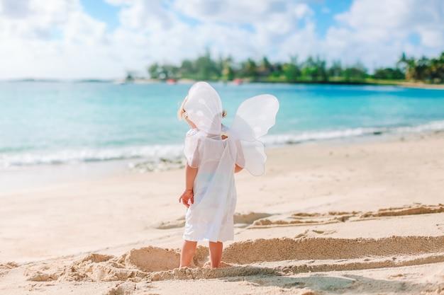 Linda garota usando asas de anjo na praia