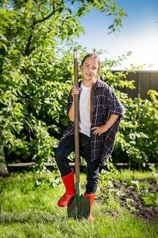 Linda garota usando gumboots vermelhos segurando uma pá no jardim