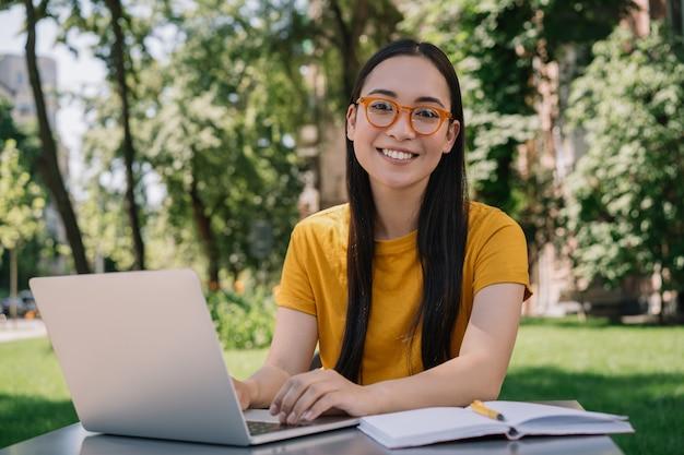 Linda garota usando óculos elegantes, olhando para a câmera. aluno estudando, ensino à distância