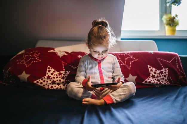 Linda garota usando smartphone na cama