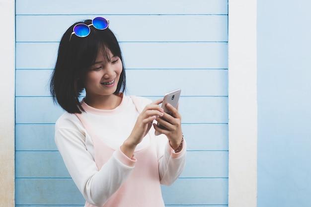 Linda garota usando telefone celular no tempo livre com feliz Foto Premium