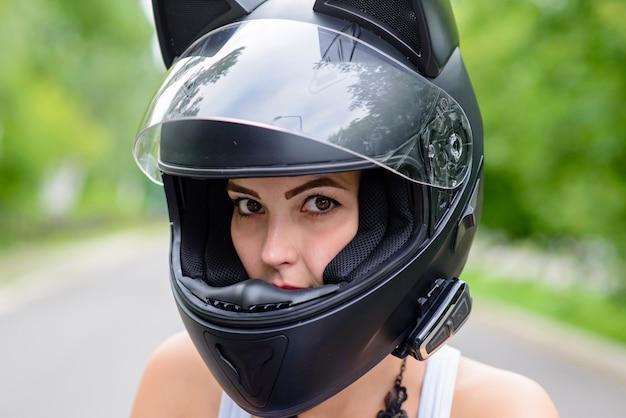 Linda garota usando um capacete. motocicleta.