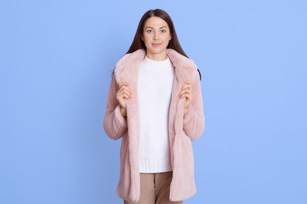 Linda garota usando um casaco de pele falsa rosa claro