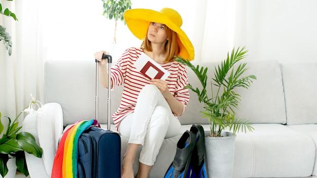 Linda garota usando um chapéu amarelo fica em casa e planeja uma viagem de férias. mala e nadadeiras para mergulho.